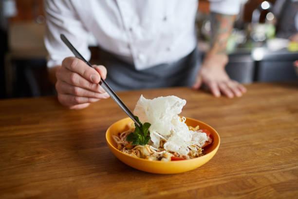 küchenchef serving asian food - kochkunst stock-fotos und bilder