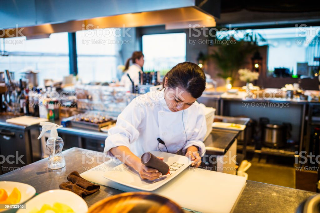 Chef serving dishes in the kitchen stock photo