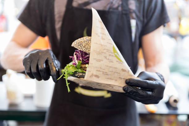 Chef serviert Bio-vegetarischen Fisch Burger auf internationalen städtischen Street food Festival. – Foto