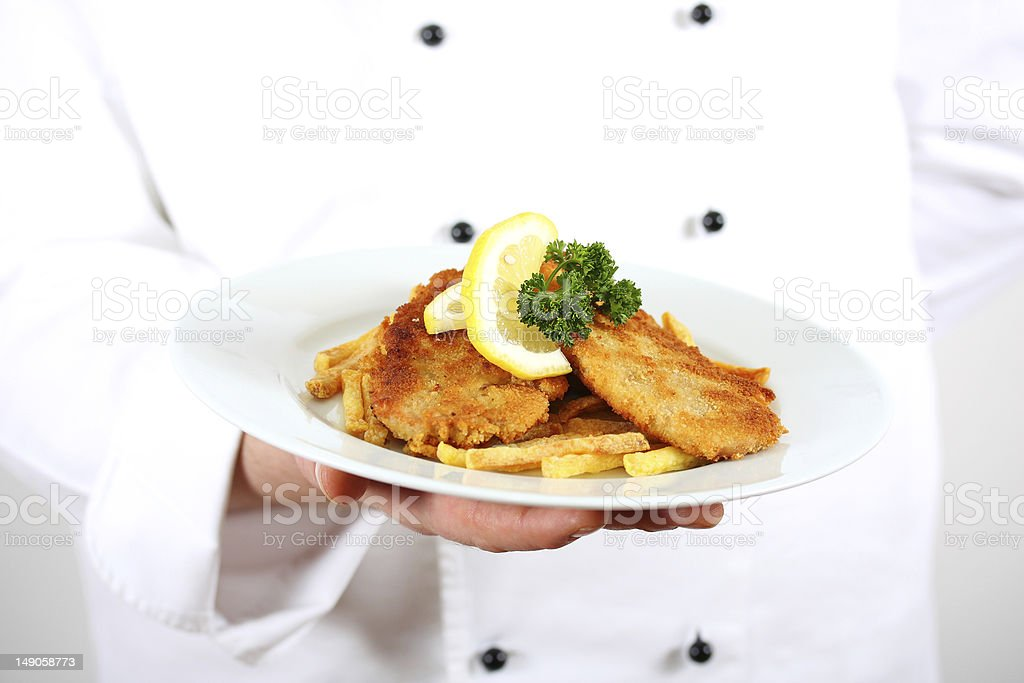 chef serving schnitzel (escalope vienna style) royalty-free stock photo
