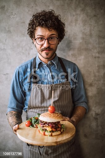 Young Man serving Burgers At Kitchen