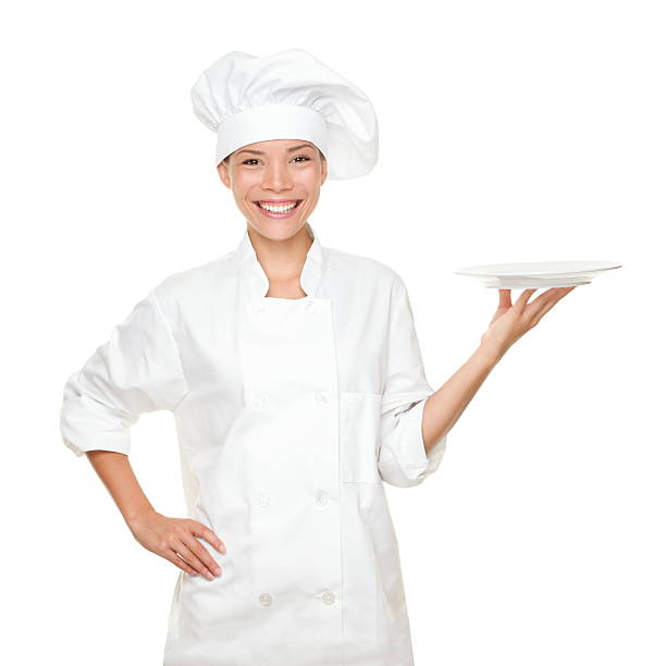 Chef showing empty plate Chef showing empty plate. Happy smilng portrait of female in chef uniform and chef hat isolated on white background. Asian Caucasian xwoman model. chef's whites stock pictures, royalty-free photos & images