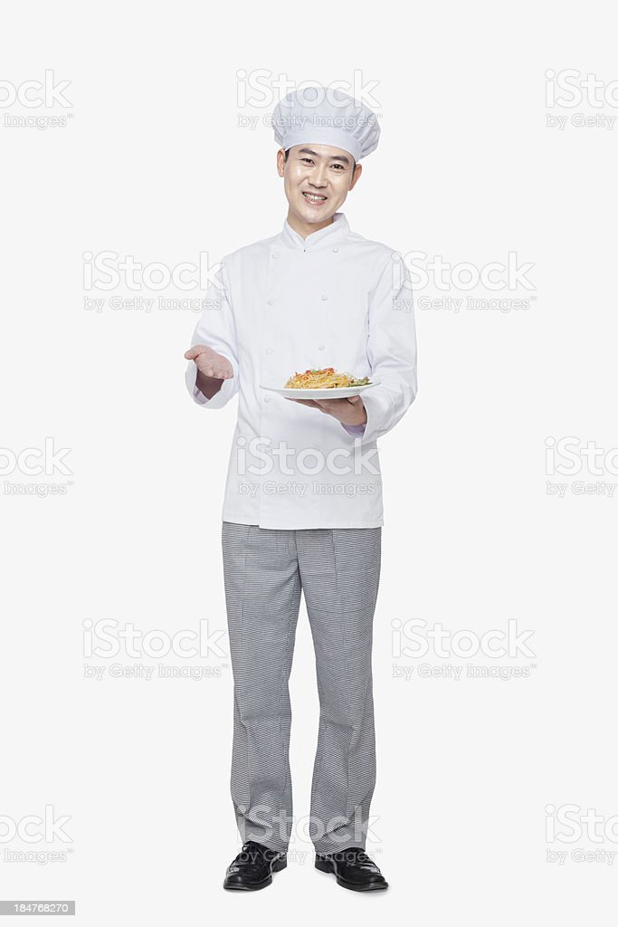 Chef showing prepared food, studio shot stock photo