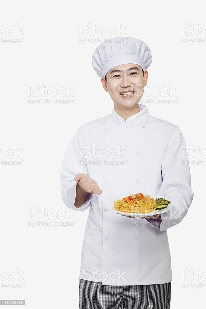 Chef showing prepared food, studio shot royalty-free stock photo