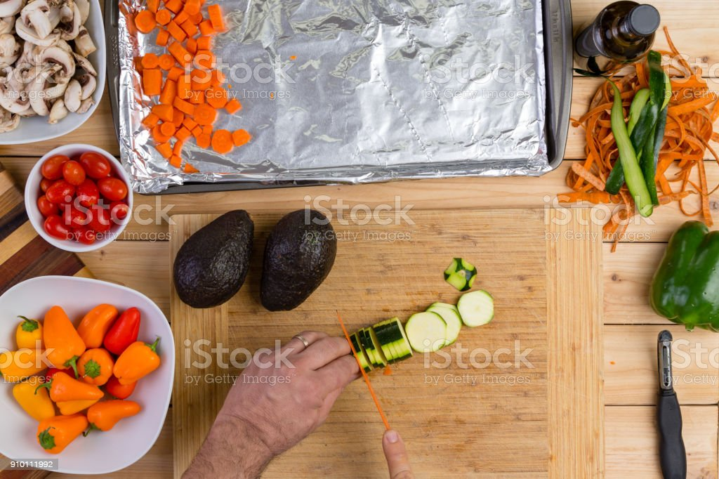 Chef slicing a fresh zucchini or courgette stock photo