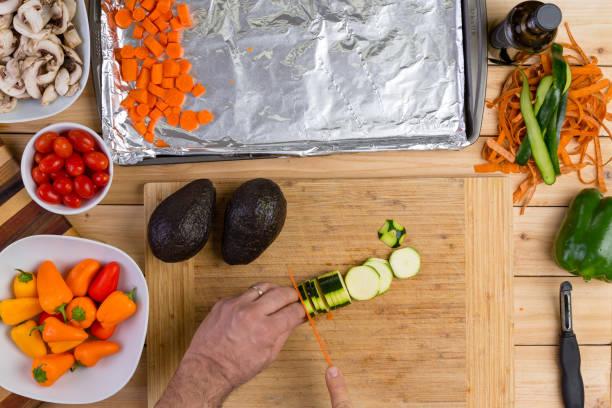 küchenchef, schneiden, eine frische zucchini oder zucchini - alufolie backofen stock-fotos und bilder