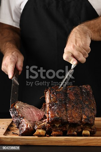 A close up vertical photograph of a chef slicing off the end piece of a freshly cooked prime rib. Isolated in black.