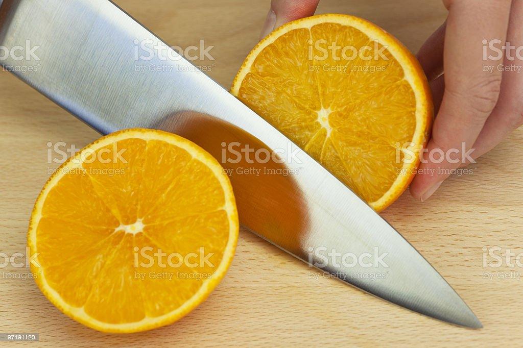 Chef Slicing Fresh Orange With Sharp Kitchen Knife royalty-free stock photo