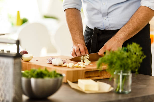 Chef slicing garlic on cutting board stock photo