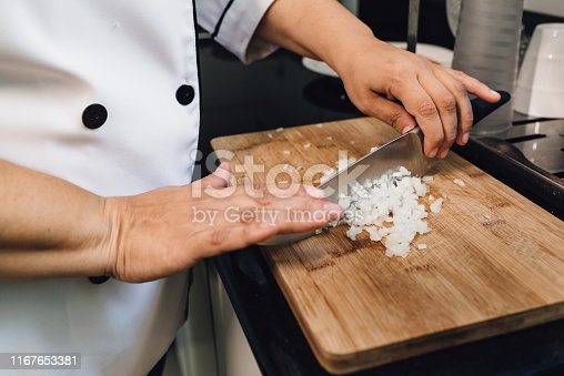 Chef slicing onion on cutting board