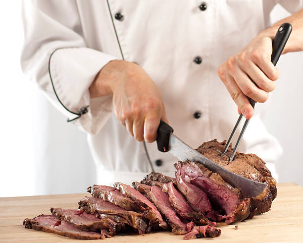 Chef slicing roast beef using carving knife and fork Professional chef carving slices of a perfectly cooked medium rare prime rib roast beef using a carving knife and fork in a commercial kitchen that could be at a restaurant, hotel, cooking school, café or catering operation in the food and beverage industry. roasted prime rib stock pictures, royalty-free photos & images