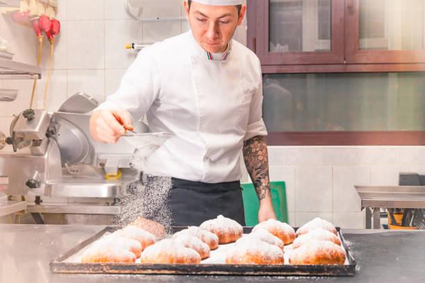koch frisch gebackenen croissants puderzucker aufsprühen - italienische küchen dekor stock-fotos und bilder