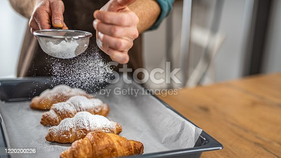 Close-up of chef's hand sprinkling powdered sugar on croissant with sieve in kitchen.