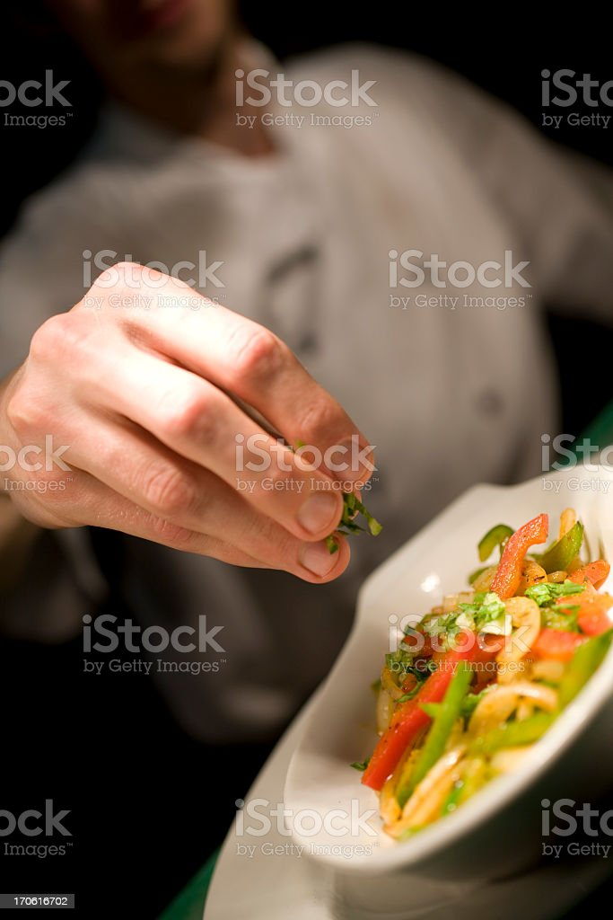 Chef sprinkling seasoning stock photo