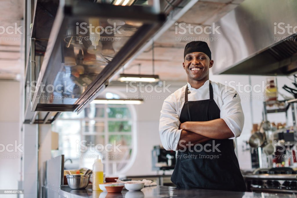 Chef standing at restaurant kitchen stock photo