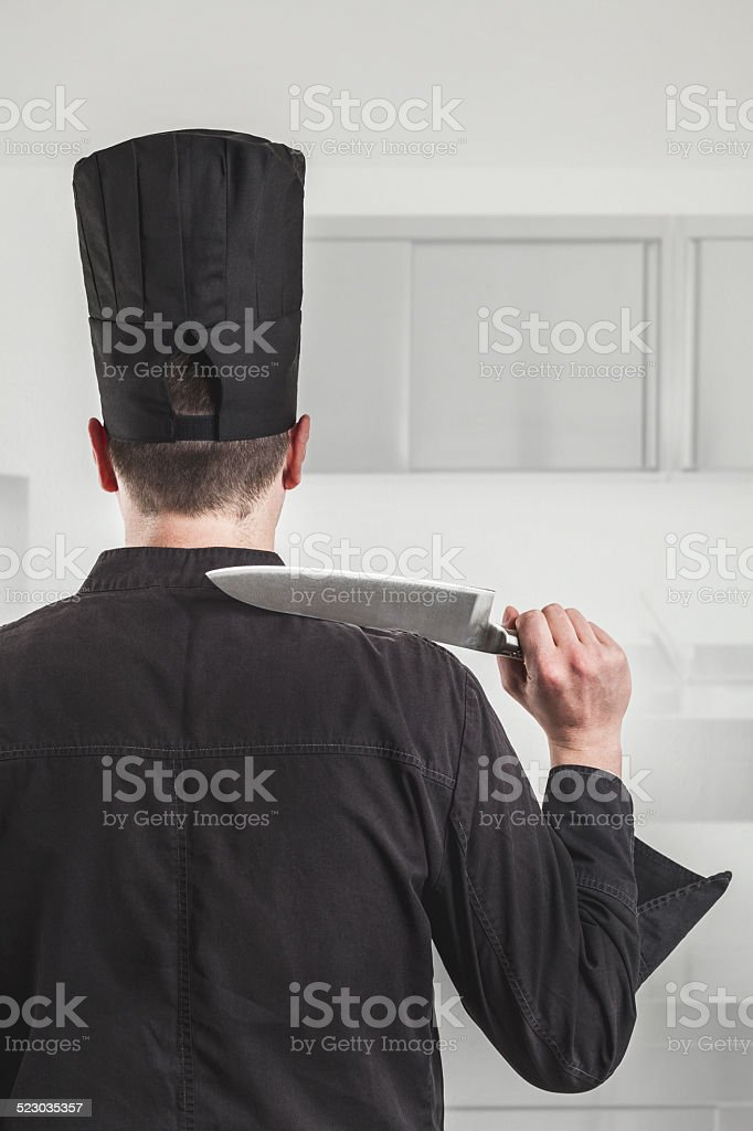 Chef standing in the kitchen with a large knife stock photo