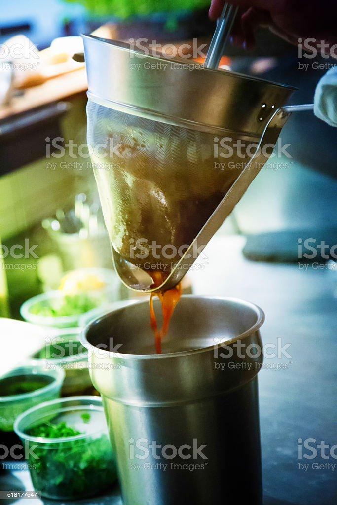 Chef straining sauce in restaurant kitchen stock photo