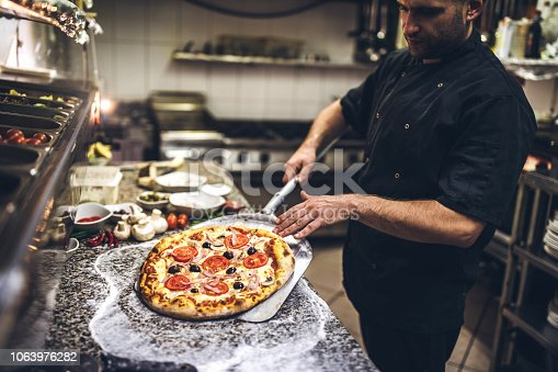 Young Chef Preparing Pizza In Kitchen Restaurant