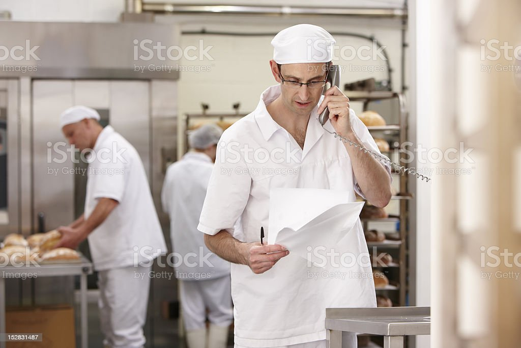 Chef talking on phone in kitchen stock photo