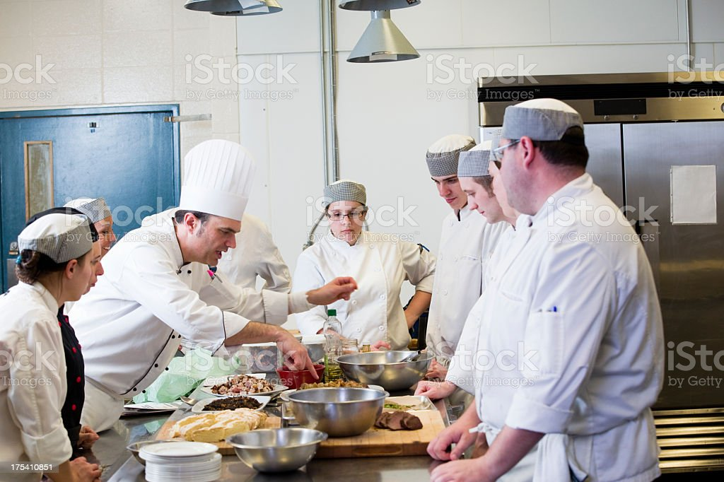 Chef teaches his new crew about food prep in kitchen stock photo