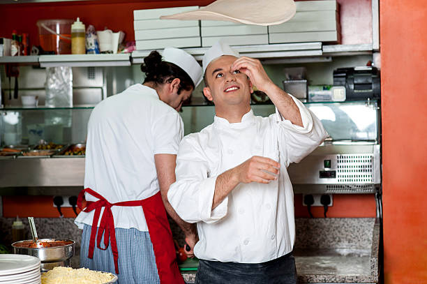 Chef throwing the pizza base dough stock photo