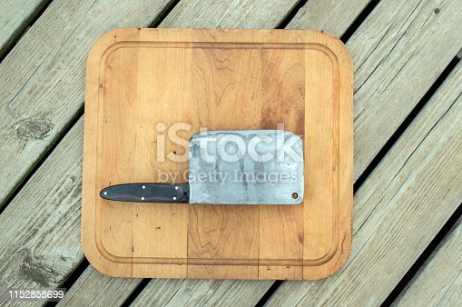 A meat cleaver and cutting board are some of the necessary tools for chef work whether cooking inside or barbecueing outdoors. Bokeh effect.