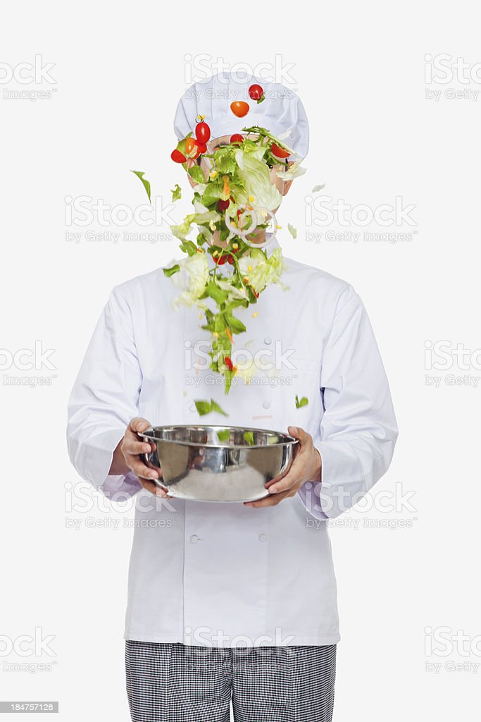 Chef tossing a salad, studio shot stock photo