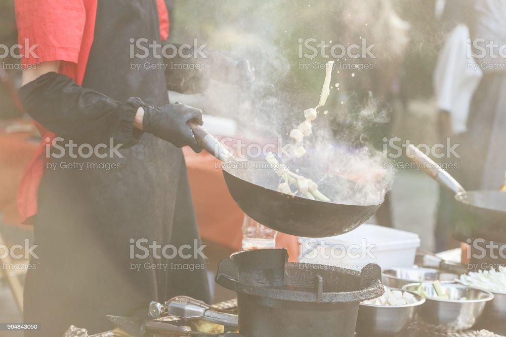 Chef tossing up ingredients in cast iron wok royalty-free stock photo