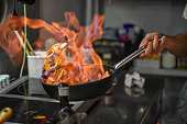 Chef tossing vegetables flambe in a pan over the burner