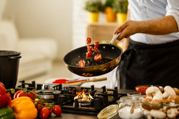 Chef tossing vegetables from cooking pan stock photo
