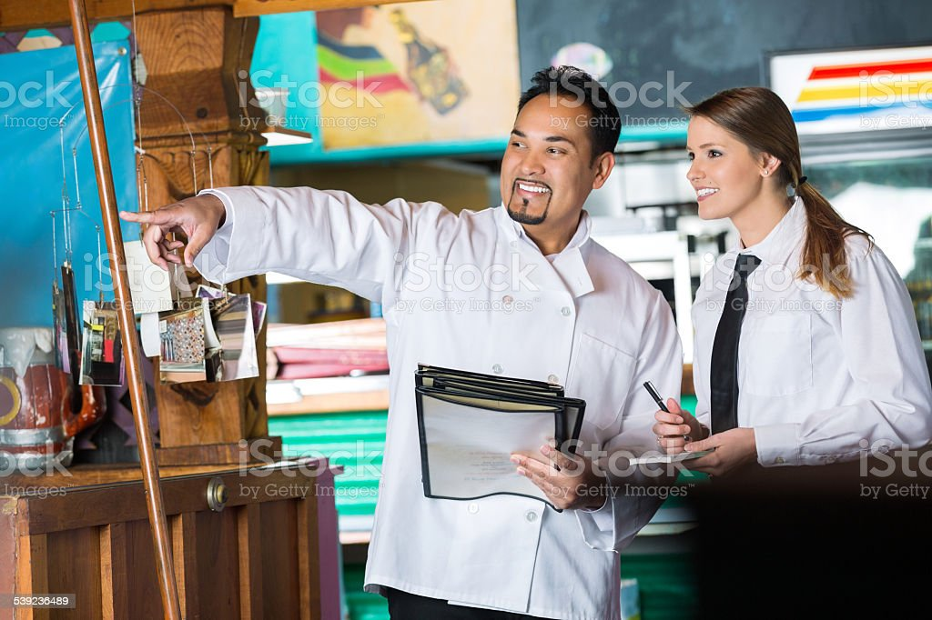 Chef training waitress in local Tex-Mex restaurant stock photo