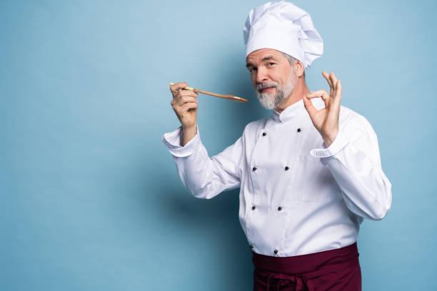 Chef versuchen Mahlzeit. Zuversichtlicher reifer Koch in weißer Uniform versucht, aus Holzlöffel zu essen und steht vor blauem Hintergrund. – Foto