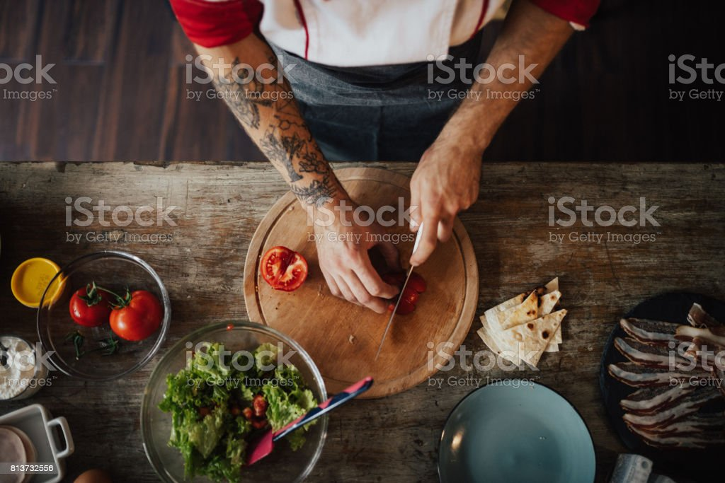 Chef uses the knife to slice tomato into smaller pieces for salad stock photo