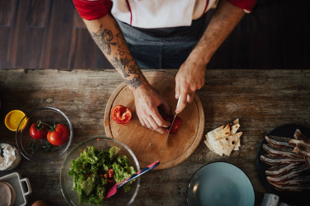 unser chef schöpft das messer scheibe tomate in kleinere stücke für salat - essen tattoos stock-fotos und bilder
