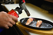 トーチを使用したシェフが味噌ソースで焼く-サーモン西京寿司
