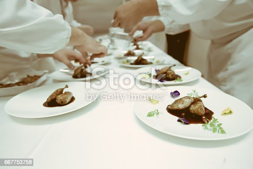 istock chef using chopsticks tong sliced beef put on the white plate in luxury dinner party, Blurry background with vintage color style. 667753758