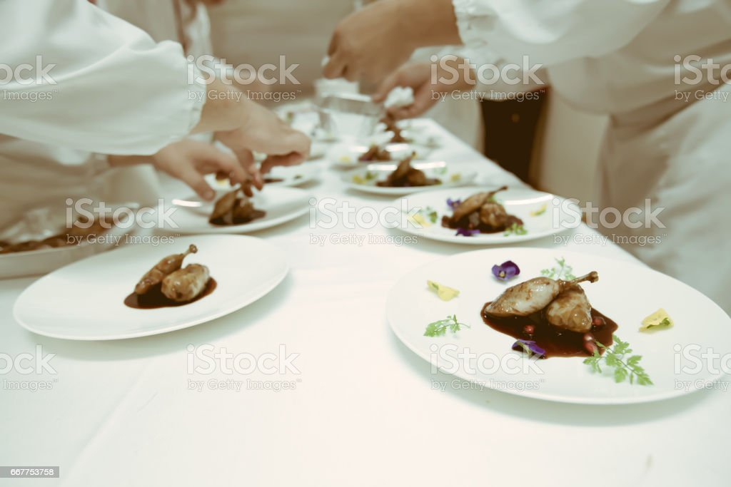 chef using chopsticks tong sliced beef put on the white plate in luxury dinner party, Blurry background with vintage color style. stock photo