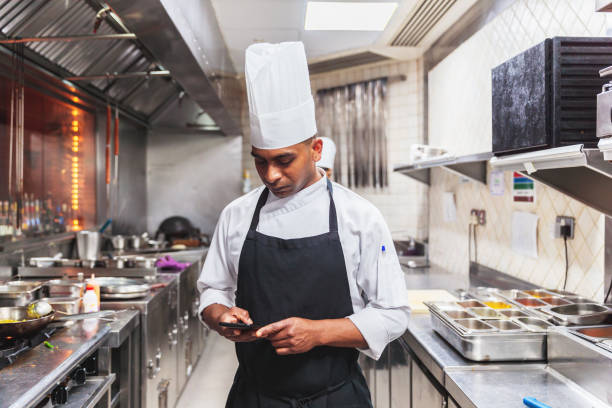 chef using phone to check a message during break - foodie stock photos and pictures