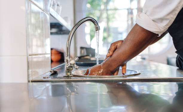 Chef washing his hands in commercial kitchen stock photo