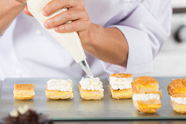 Chef with a pastry bag Chef decorating with a pastry bag with cream icing bag stock pictures, royalty-free photos & images