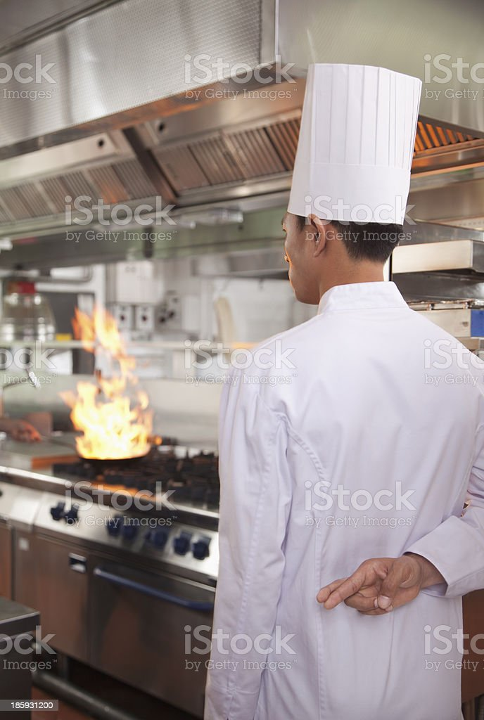 Chef with Fingers Crossed as a Pan Catches Fire royalty-free stock photo