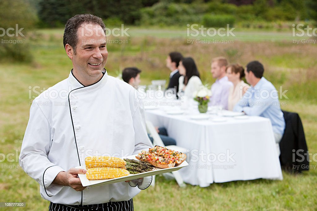 Chef with meal and people at dining table in a field stock photo