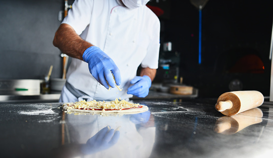 Skilled chef preparing traditional italian pizza  in interior of modern restaurant kitchen with special wood-fired oven. Wearing protective medical face mask and gloves in coronavirus new normal concept