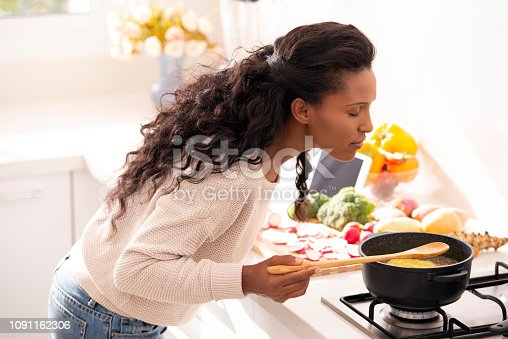 Cook woman enjoying the smell of freshly cooked soup, using a wooden spoon to taste the vegetarian soup. The woman with long black hair wearing a casual beige sweater and jeans.