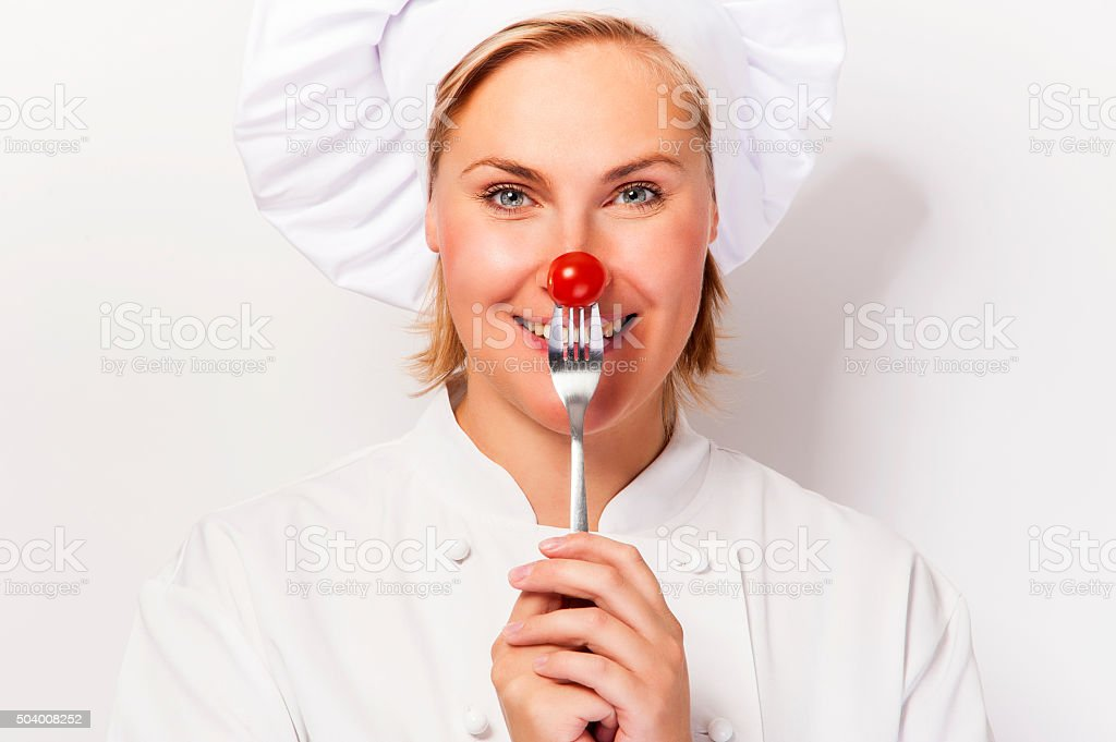 Chef woman holding a fork with tomato against her nose. stock photo