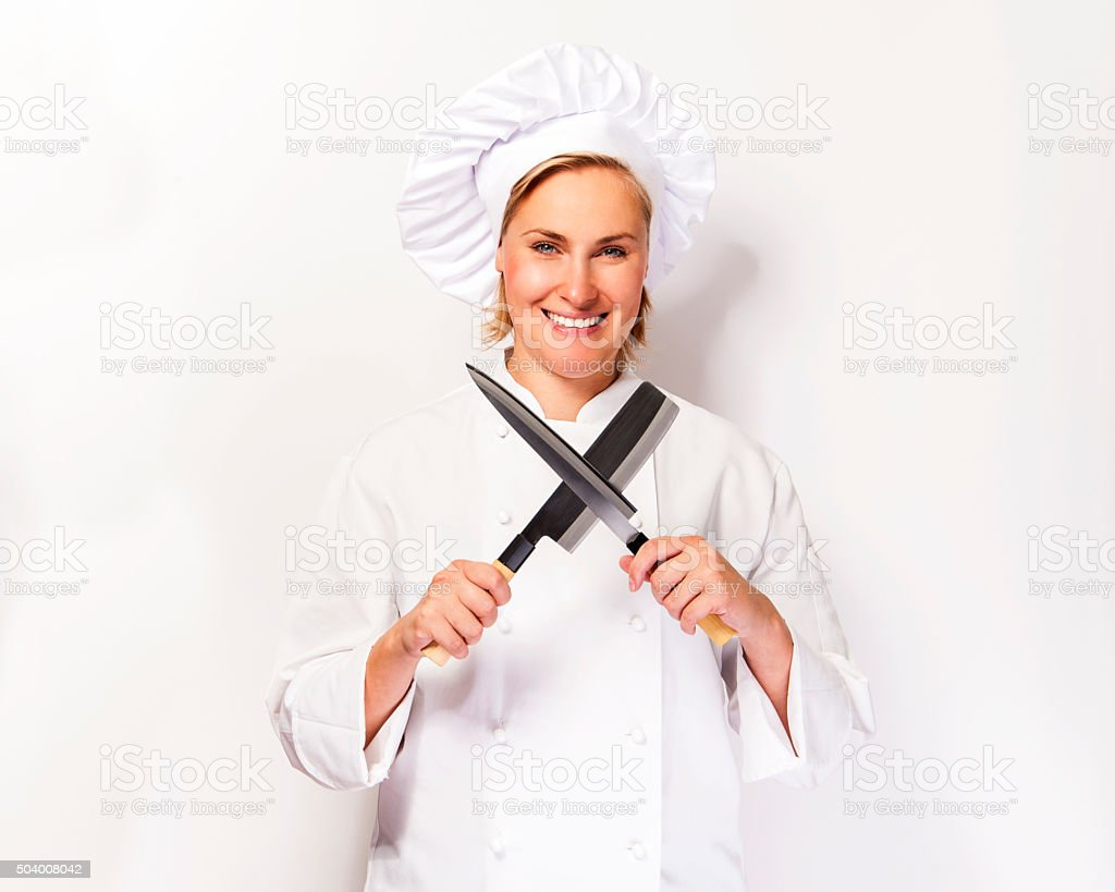 Chef woman on white background with knifes crosed. stock photo