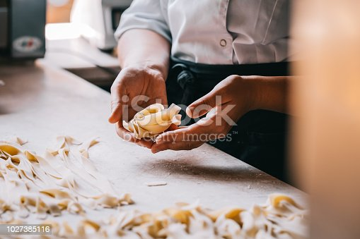 Chef woman's hands making tagliatelle pasta. Cooking process. Raw food photography concept.