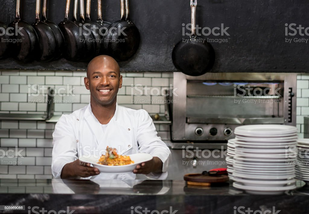 Chef working in a kitchen and showing his plate stock photo