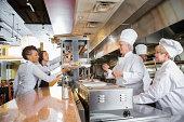 Chefs and waitstaff working together in busy restaurant kitchen