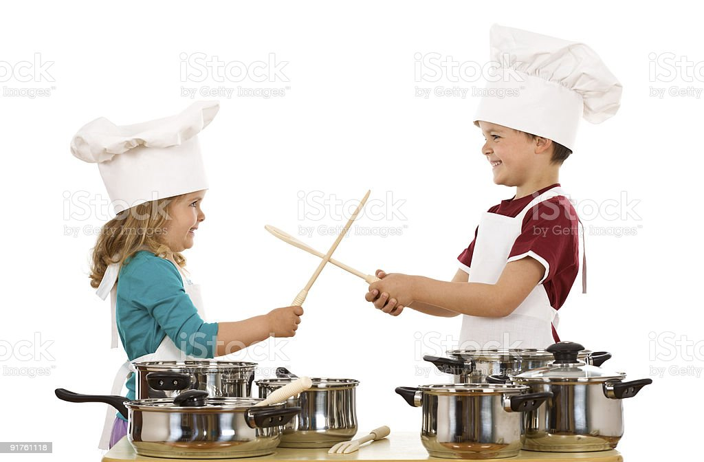 Chefs duel with wooden utensils royalty-free stock photo